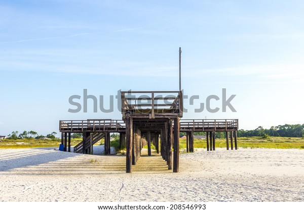 wooden pier at Dauphin Island in afternoon sun