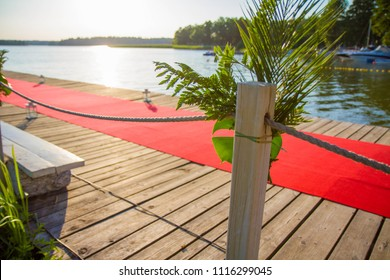 A wooden pier decorated with a red carpet, flowers and lampions