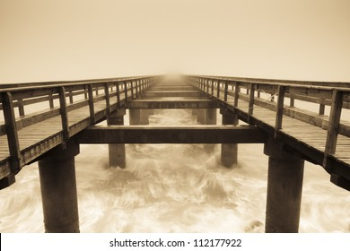 Wooden pier in the fog. Brown color. White waves around. Romantic.
