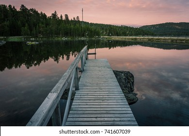 Wooden Pier in Inari Lake during the magical midnight sun, violet sky, lapland, finland