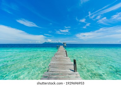 A wooden pier or jetty heading toward the horizon on a crystal clear sea water beach at Pom Pom Island Sabah, overlooking the Boheydulang Island.