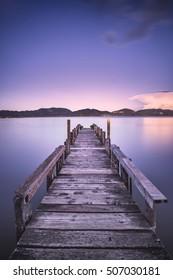 Wooden pier or jetty on blue lake sunset and sky reflection water. Long exposure, Versilia Massaciuccoli, Tuscany, Italy.