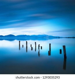 Wooden pier or jetty remains on blue lake sunset and sky reflection water. Long exposure, Versilia Massaciuccoli, Tuscany, Italy.