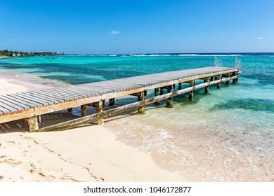 A wooden pier juts into the Carribbean on Spotts Beach in Savannah on the South side of Grand Cayman, Cayman Islands
