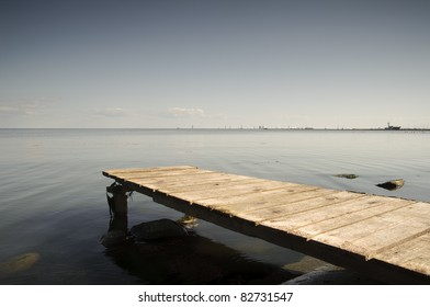 A wooden pier juts out into the Curonian Lagoon at Nida, Lithuania, on the Curonian Spit. Sailing boats and the marina at Nida are visible on the horizon.