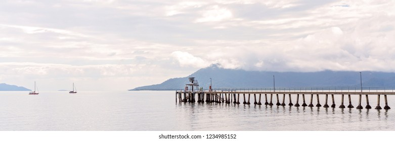 Wooden pier jutting out into the ocean on a calm day with mountain background and cloudy sky