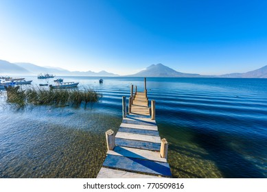 Wooden pier at Lake Atitlan on the shore at Panajachel, Guatemala.  With beautiful landscape scenery of volcanoes Toliman, Atitlan and San Pedro in the background.