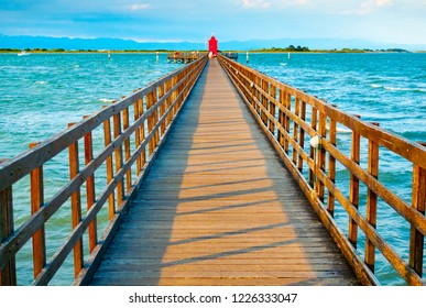Wooden pier leading to a red lighthouse at sunset in Lignano Sabbiadoro, Friuli, Italy