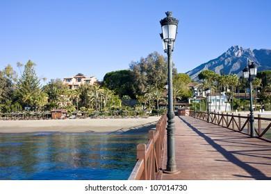Wooden pier in Marbella, resort town on Costa del Sol in Spain, Andalucia region, Malaga province.