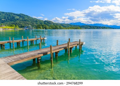 Wooden pier for mooring boats on Worthersee lake on beautiful summer day, Austria
