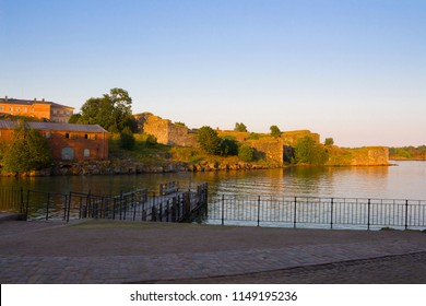 A wooden pier and old historical stone fortifications of Fort Suomnelinn in the Gulf of Finland near the city of Helsinki at the end of a summer day.