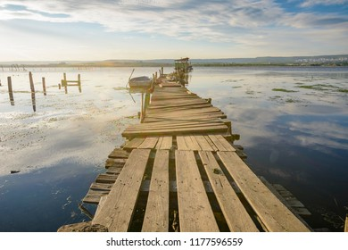 Wooden pier on a lake with a fishing hut. sunset with calm water