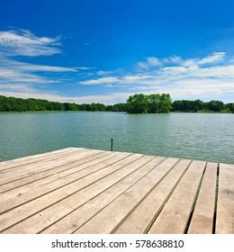 Wooden Pier on Lake under Blue Sky in Summer Landscape