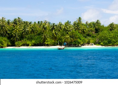 Wooden pier on a paradisaca island of Maldives with turquoise sea and surrounded by palm trees