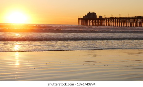 Wooden pier on piles, silhouette at sunset, California USA, Oceanside. Waterfront resort, pacific ocean tide, tropical beach. Summertime coastline vacations atmosphere. Sunny sea waves at sundown.