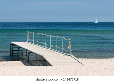 Wooden pier on the sandy beach over the green sea