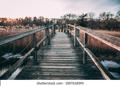 A Wooden Pier Over A Salt Marsh In Winter