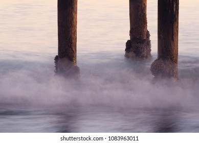 Wooden pier pilings with blurred crashing waves
