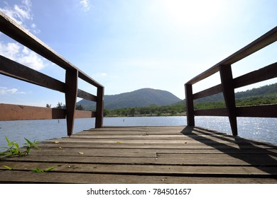 wooden pier at the riverside with mountain landscape