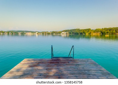 Wooden pier with staircase into clear turquoise water of Klopein Lake in Carinthia, Austria