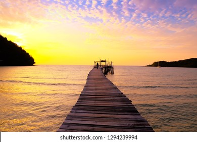 Wooden pier stretches to the sea of sunset against blue sky.Beautiful tropical beach.
