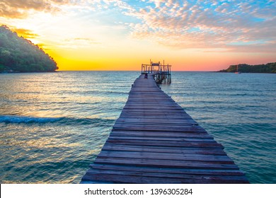 Wooden pier stretches to the sea of sunset against blue sky.Beautiful tropical beach