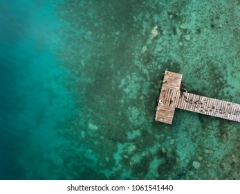 Wooden pier and turquoise water from above - shot from a drone