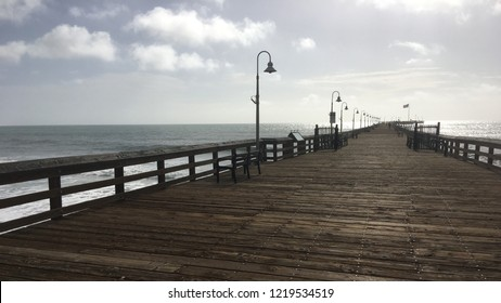 Wooden pier at Ventura Beach with Pacific Ocean in background. South California on a day with scattered clouds