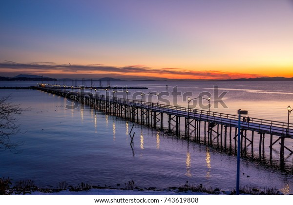 Wooden pier at White Rock, BC, Canada extends diagonally into image... its twinkling lights reflected in the sea.  The sun is setting with flaming reds and oranges over the Gulf and San Juan Islands