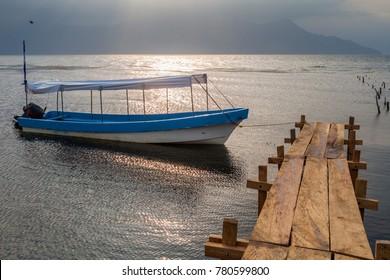 Wooden piers and a boat at lake Yojoa, Honduras