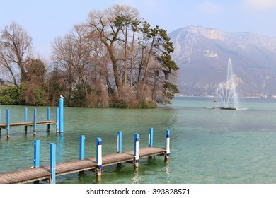 Wooden piers extend into a crystal clear alpine lake, Lake Annecy, where fishing boats dock in the city of Annecy, France.
