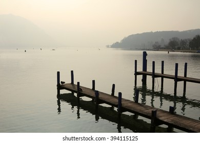 Wooden piers extend into a crystal clear alpine lake, Lake Annecy, in the early morning light. The piers are used by fishing boats to dock in the city of Annecy, France.