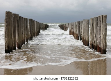 Wooden piles or groynes. The breakwaters at the coast of the Netherlands. Photo made on the beach between Domburg and Oostkapelle at a cloudy and stormy day. - Shutterstock ID 1751122832