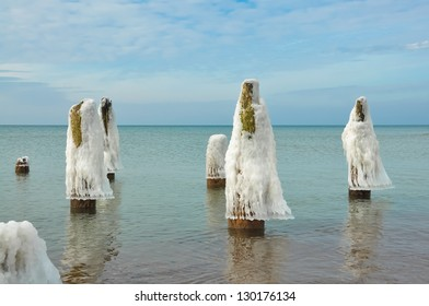 wooden piles in the sea covered with ice and snow