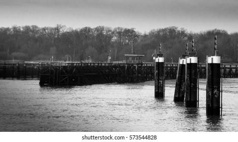 Wooden pillars in a calm river Scheldt nearby the Port of Antwerp