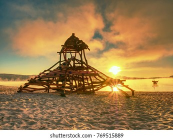 Wooden pillars playground with a wooden tower. Pirate bay built in sand of holiday resort.  Calm water of lake.