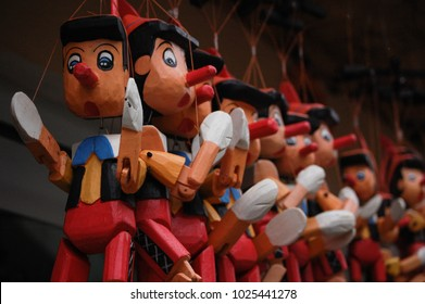 Wooden pinocchio style dolls for sale in Turkish outdoor market.