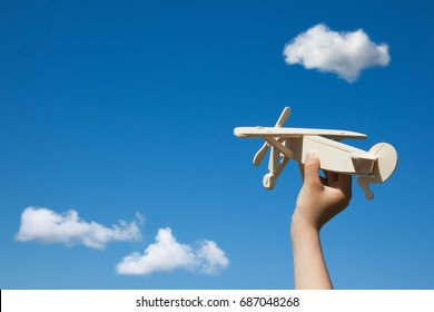 Wooden plane in child hand on the blue sky and clouds background. ( With space for text.)
