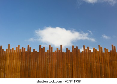 Wooden plank wall with blue sky in the background.
