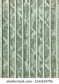 Wooden plank wall painted in green tones with texture as background.