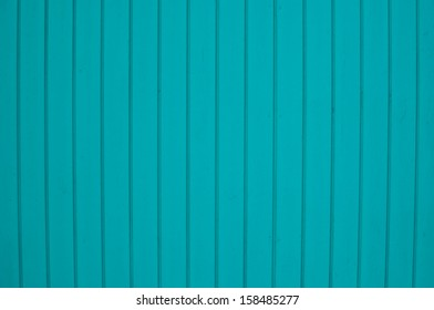 Wooden plank wall painted pretty turquoise colors.