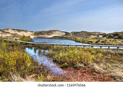 Wooden plankbridge across a small lake in a sandy dune area with low shubs on the German Northsea island of Amrum