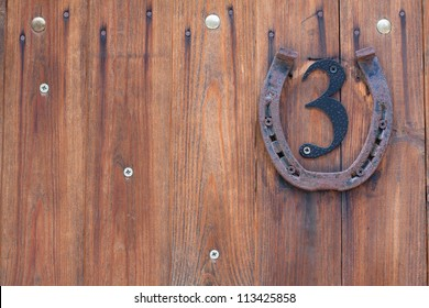 Wooden planks background with metal number three and rusty horseshoe