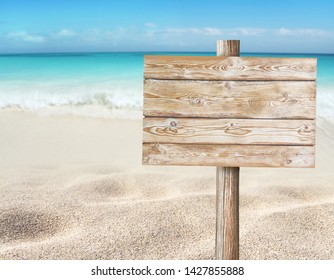 Wooden planks sign board on the beach blurred background. Tropical island paradise. Sandy shore washing by the wave. Bright turquoise ocean water.
