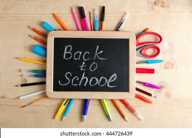 """wooden plaque with the inscription """"back to school"""" near stationery on a brown wooden background"""
