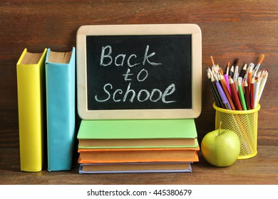 """wooden plaque with the inscription """"back to school"""" near the pencil box with school equipment and Apple with stack of books and notebooks on brown wooden background"""
