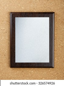 Wooden plaque with silver plate on cork background