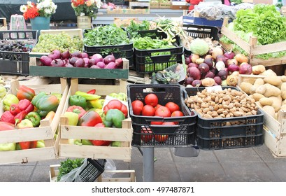 Wooden and plastic crates with piles of fresh organic fruits and vegetables sold on street market