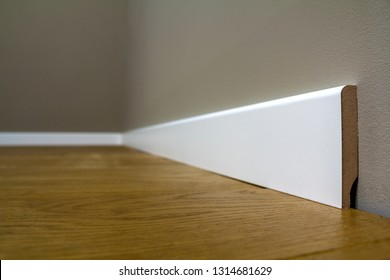 Wooden or plastic white floor plinth installation in big empty room on wooden floor and white plastered stucco walls background. Interior details.