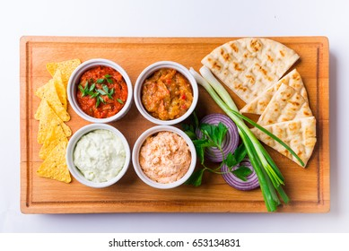 wooden plate with appetizers and bread. souses and salads.
